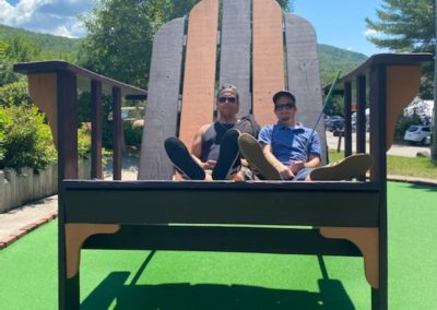 2 guys sitting on a large outdoor chair